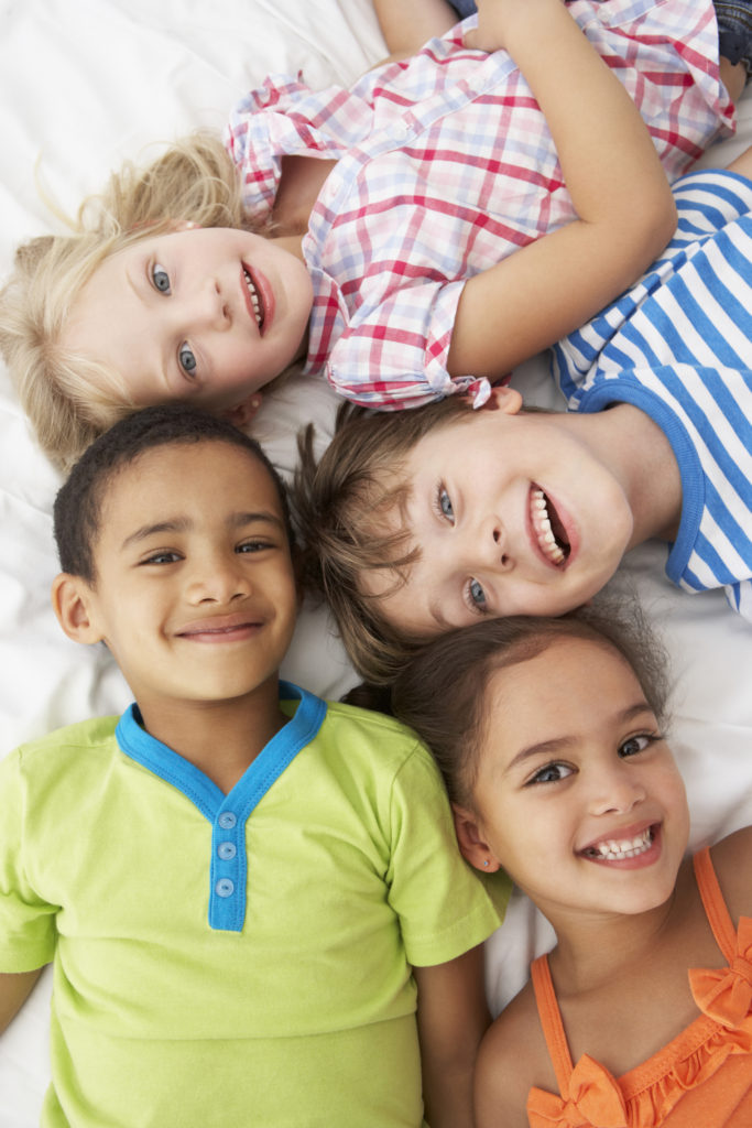 Overhead View Of Four Children Playing On Bed Together Smiling Up At Camera